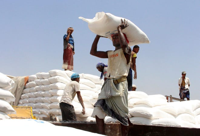 FILE - In this Sept. 21, 2018 file photo, men deliver U.N. World Food Program (WFP) aid in Aslam, Hajjah, Yemen. The World Food Program on Friday, Oct. 9, 2020 won the 2020 Nobel Peace Prize for its efforts to combat hunger and food insecurity around the globe.