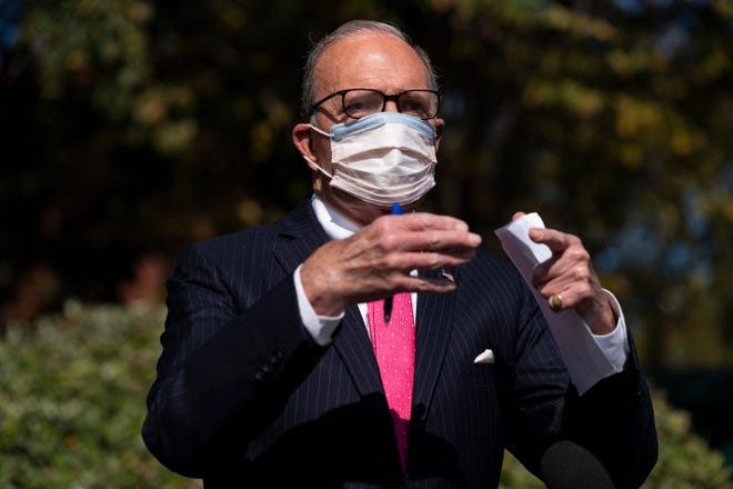 White House chief economic adviser Larry Kudlow talks Friday with reporters outside the White House about coronavirus relief package negotiations in Washington.