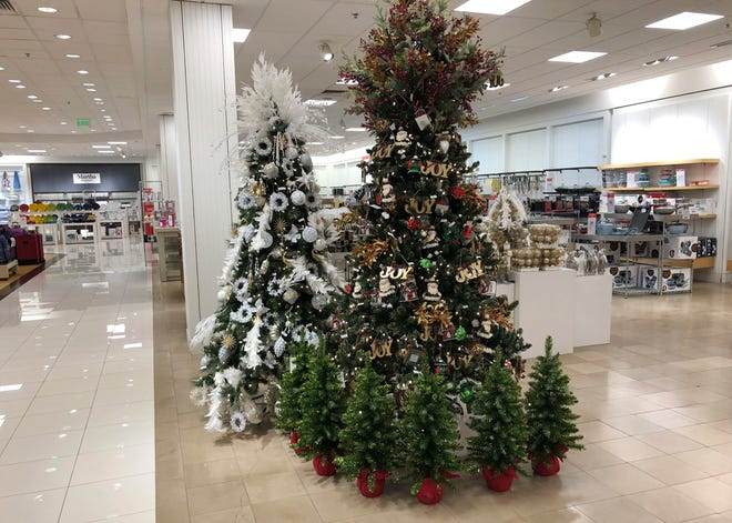 A display of Christmas trees stands next to holiday knick-knacks on display in a Macy's department store.