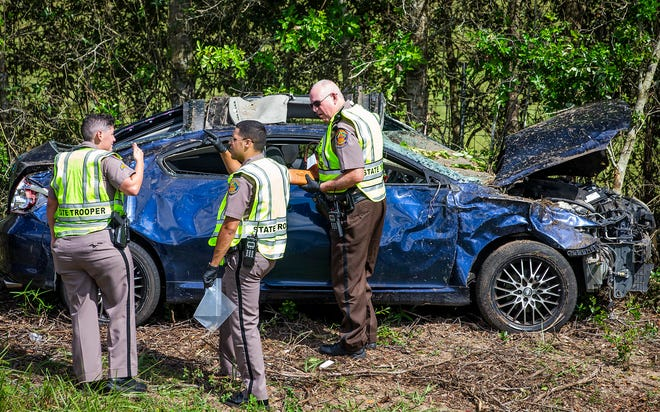 Florida Highway Patrol Trooper Jessica Sabo, left, talks with Trooper Justin Loney, center, and Auxiliary Trooper Richard Young, right, at the scene of a fatal accident on I-75 about 5 miles south of the State Road 200 exit on Friday at about noon. The car collided with a tractor trailer truck, left the road, overturned and ejected the driver who died at the scene.