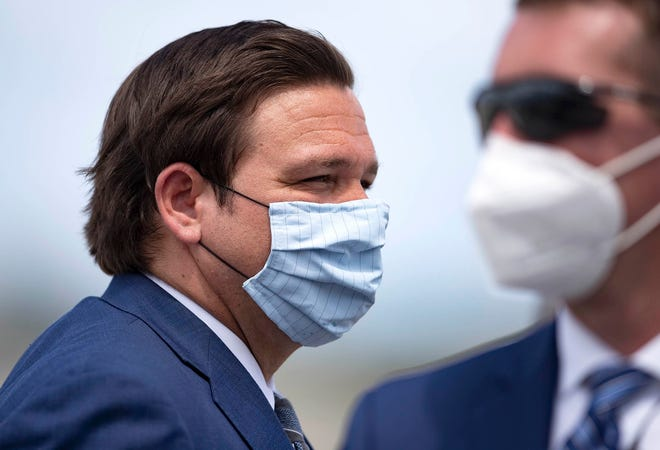 A masked Gov. Ron DeSantis prepares Sept. 8 to greet President Donald Trump, who flew into Palm Beach International Airport that day to give a speech in Jupiter.