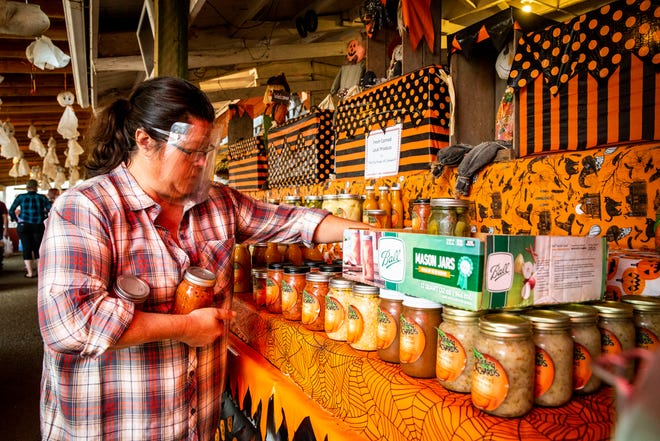 Pamla Fritts, also known as The Duchess of Cansalot, stocks her inventory at Detering Orchards in Harrisburg, Ore., on Oct. 4, 2020 during the second weekend of Apple Daze, an apple festival.