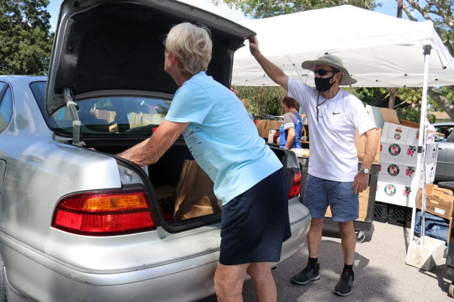 Volunteers Beatty Shipley and Richard Durham fill a trunk with bags of groceries at St. Wilfred Episcopal Church's drive-through food pantry Friday afternoon. The food pantry is serving nearly 200 families in Sarasota and DeSoto counties.