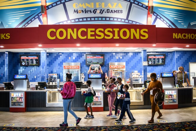 After getting snacks, Theresa Rueben, right, and children head to their movie at Omni Cinemas 8 on its first day back open Friday. The theater was closed for months because of the COVID-19 pandemic.