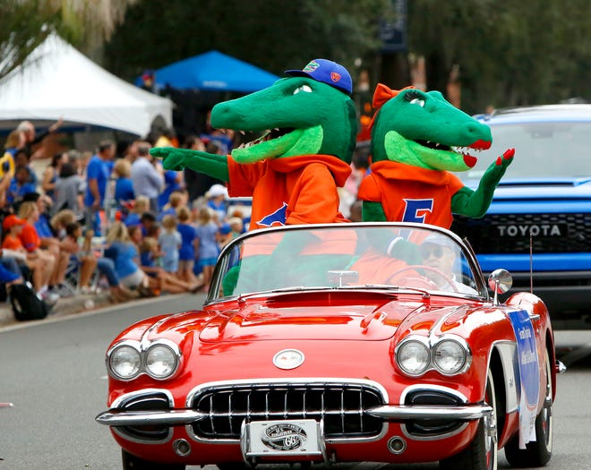 Mascots Albert and Alberta wave to fans during the 2018 UF homecoming parade. This year's parade has been canceled due to the COVID-19 pandemic, and officials are asking campus organizations, businesses and residents to decorate their homes or properties in Gator fashion.