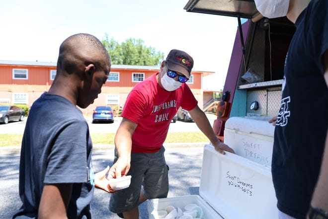 Mike Manfredi, center, the owner of Sweet Dreams ice cream shop, hands a scoop of ice cream at the Village Green Apartments in Gainesville on April 21.