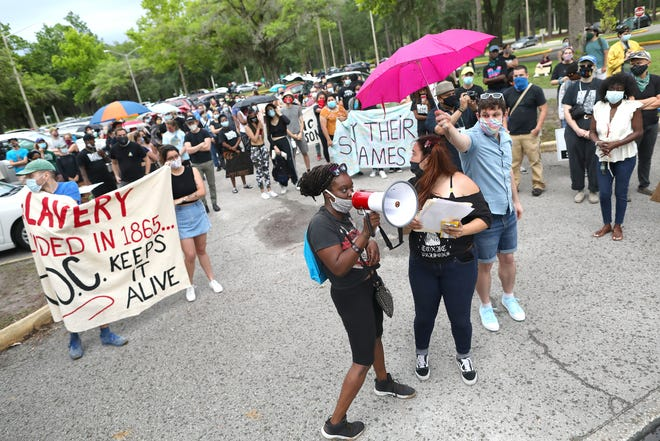 Protesters shout the names of inmates in the Alachua County Jail as a coalition of groups gather to protest forced labor, abuse and brutality during a June 19 event.