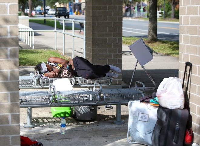 A homeless woman sleeps on a bench near some of her belongings outside the Alachua County Courthouse just off Main Street in downtown Gainesville on Oct. 8.