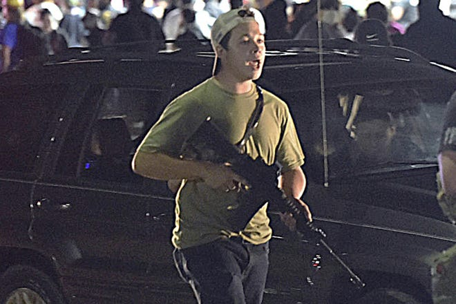 "In this Tuesday, Aug. 25, 2020, file photo, Kyle Rittenhouse carries a weapon as he walks along Sheridan Road in Kenosha, Wis., during a night of unrest following the weekend police shooting of Jacob Blake. In a document filed Thursday, Oct. 8, 2020, defense attorneys say sending Rittenhouse, accused of killing two protesters days after Jacob Blake was shot by police in Kenosha, Wis., to stand trial in Wisconsin would ""turn him over to the mob."""