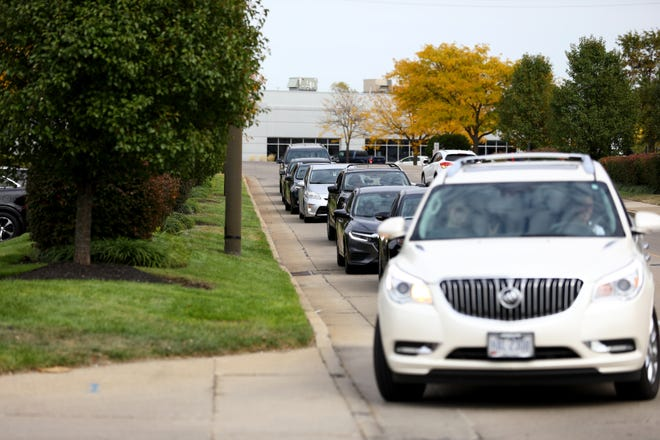 Motorists queue to enter the Hamilton County Board of Elections to either vote in person or drop off their completed absentee ballots, Friday, Oct. 9, 2020, in Norwood, Ohio.