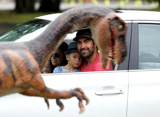 Richie Keith, 42, of Rochester. Atticus Keith, 3, Danielle Keith, and Poppy Keith, 1, check out a velociraptor on display from their vehicle during the Jurassic Quest exhibit at tDTE Energy Music Theatre in Clarkston, Mich., on Friday, Aug. 28, 2020.