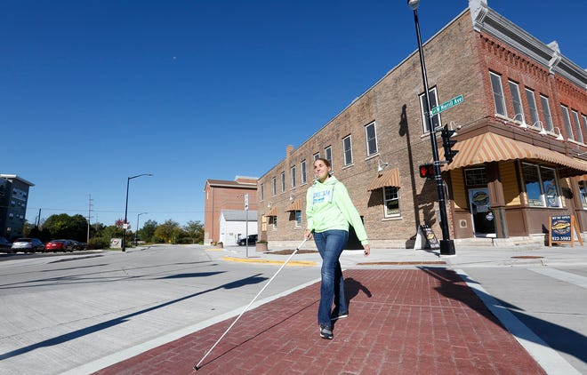 Laurie Holzmann of Fond du Lac uses an audible traffic signal Thursday,  to help her cross the intersection at Main and Merrill streets. The city installed the audible crosswalks for the visually impaired.