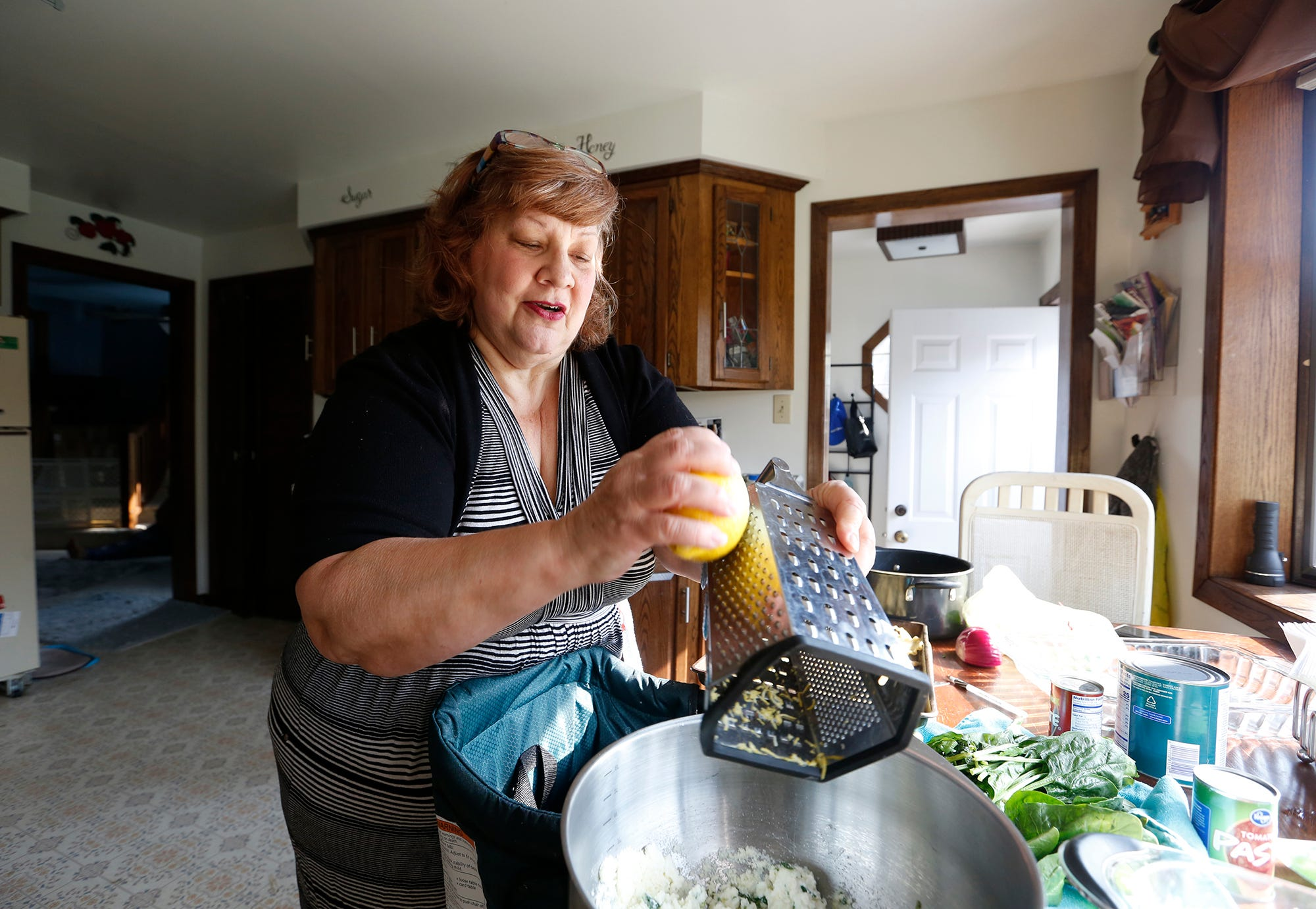 Cindy Martinez of Fond du Lac cooks lunch for her daughter and granddaughter in her kitchen. Martinez was laid off from her job this spring when COVID-19 struck. She finds fulfillment in mentoring young women who have experienced emotional trauma.