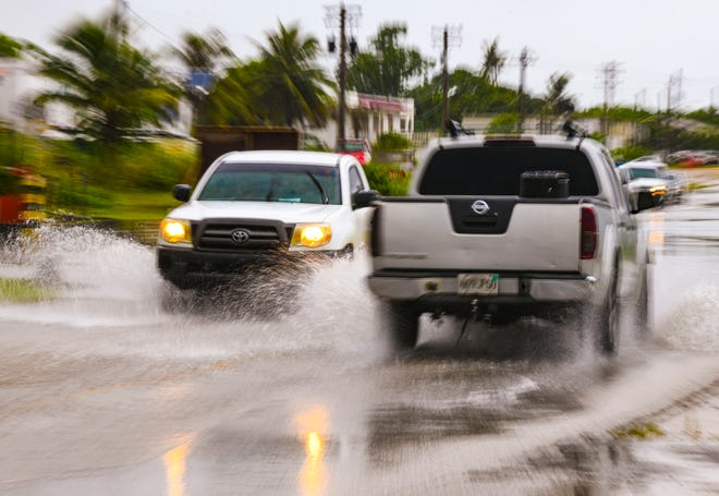 Vehicles splash each other with standing water collected on the surface of Adrian Sanchez Street, sometimes referred to as Hamburger Road, as a heavy rainshower passes through the area on Friday, Oct. 9, 2020.