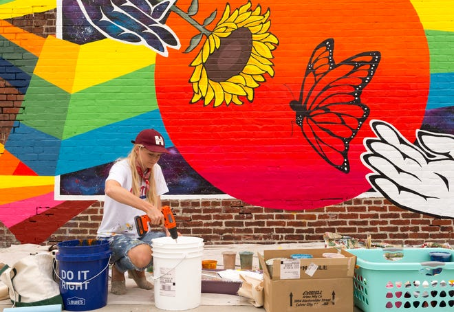Artist Maddy Fritz mixes paint as she puts the finishing touches on her mural on the back of Bugg Realty 17 S. Main Street in downtown Henderson, Ky., Thursday afternoon, Oct. 8, 2020.