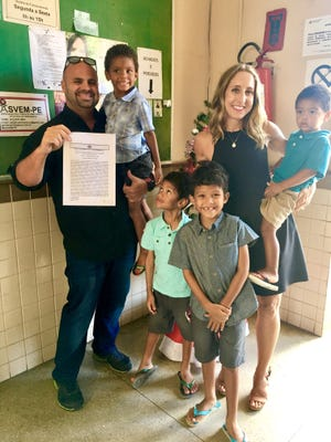 This family photo from 2016 in the courthouse lobby in Paulista, Brazil, shows the Pratts of North Liberty proudly displaying final adoption papers after two months in the country. Brandon holds Enzo and Jennifer holds William. Standing are Cristiano (left) and Leandro.