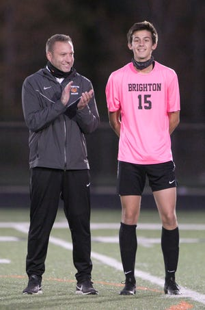Brighton soccer coach Mark Howell and junior Brennan Cheladyn are recognized as being cancer survivors before a game against Hartland on Thursday, Oct. 8, 2020.