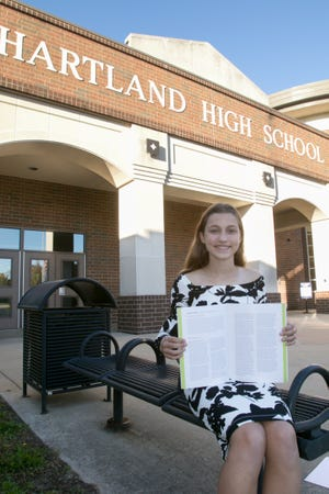 Hartland High School freshman Ashlynn Mulka is one of 20 students in Michigan who won an art and writing competition hosted by the Holocaust Memorial Center. Mulka poses with her winning essay in front of the high school Thursday, Oct. 8, 2020.