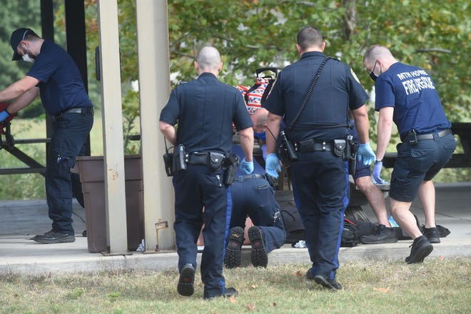 Emergency personnel tend to a stabbing victim Friday morning at a pavilion located behind the Mountain Home Church of Christ.