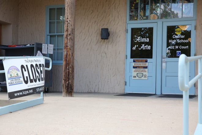 The entrance to the Alma d'Arte Charter High School in Las Cruces on Monday, Aug. 31, 2020, were decked with warnings about COVID-19 safety and a notice that the facility was closed.
