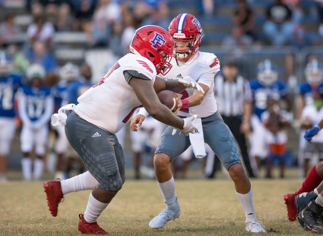 Quarterback Dalton Biggs (2) hands off to Detayvious Grandison (17) during the Pine Forest vs Washington football game at Booker T. Washington High School in Pensacola on Thursday, Oct. 8, 2020.