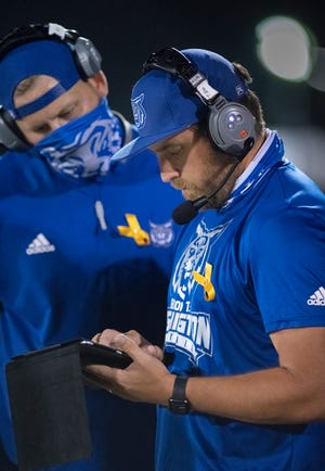 Head coach Tommy Joe Whiddon, right, checks his electronic tablet during the Pine Forest vs Washington football game at Booker T. Washington High School in Pensacola on Thursday, Oct. 8, 2020.