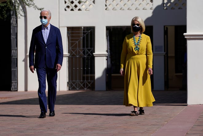 Democratic presidential candidate former Vice President Joe Biden walks with Cindy McCain as they visit the Heard Museum in Phoenix on Oct. 8, 2020.