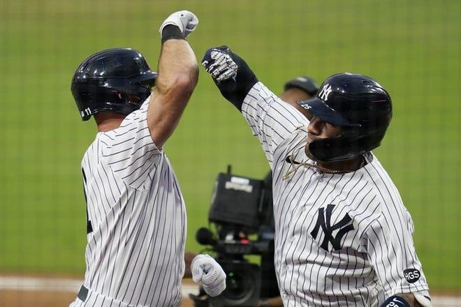 El venezolano Gleyber Torres (derecha) festeja con Brett Gardner, de los Yankees, tras remolcarlo con un jonrón en el cuarto juego de la serie divisional ante los Rays.