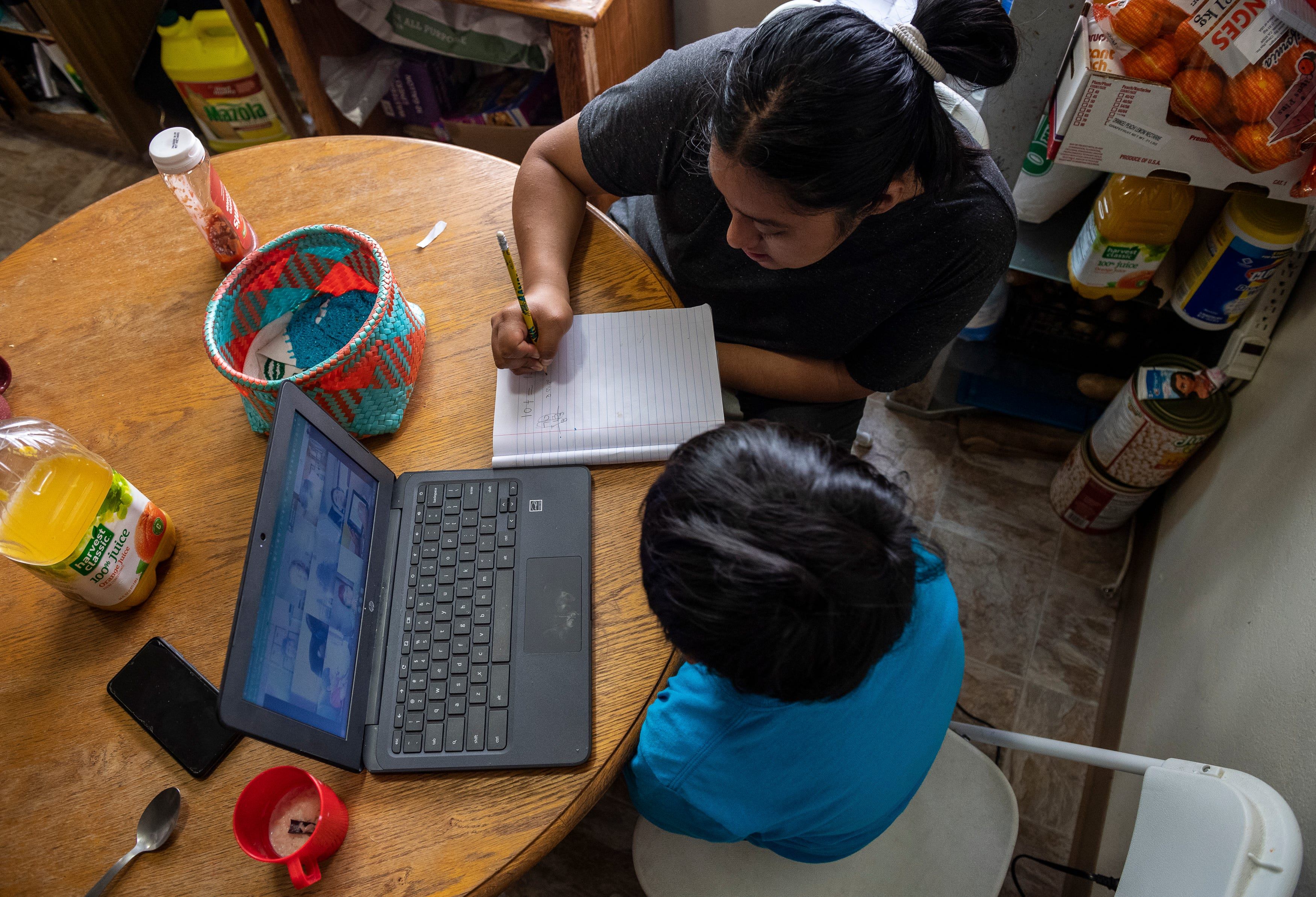 Resi Salvador, helps her younger brother Hugo Salvador, with his virtual class work in Salinas, Calif., on Thursday, Aug. 13, 2020.