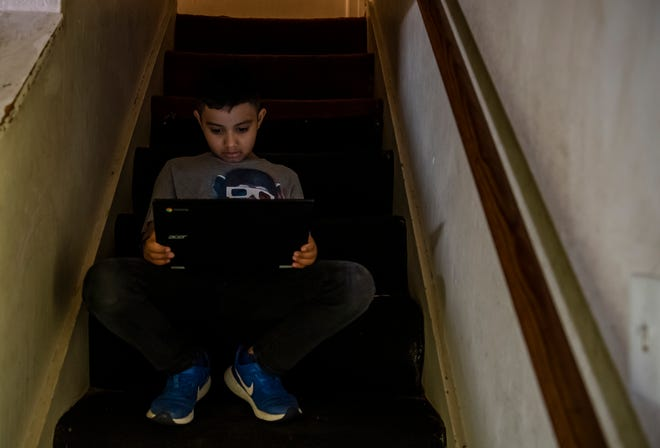 A young boy sits on the stairs and attend his virtual class inside his baby sitter's home in Salinas, Calif., on Thursday, Sept. 17, 2020.