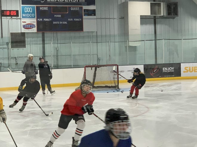 New Ice Cats coach David Bakke talks to assistant John Weber as the Cats go through drills at practice on Thursday, Oct. 8, 2020.