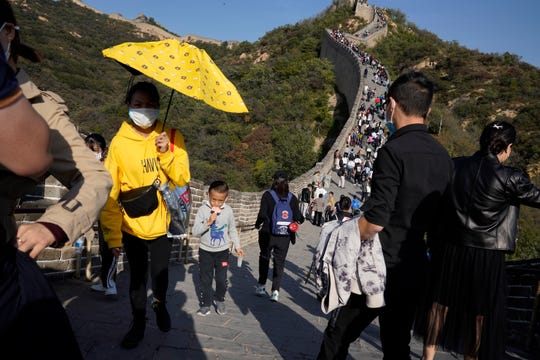 In this Oct. 6, 2020, file photo, a child lowers his mask to enjoy an ice cream as he climbs up a stretch of the Badaling Great Wall of China on the outskirts of Beijing.