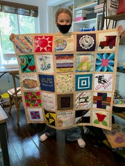 Madeleine Fugate holds up her COVID-19 Memorial quilt.