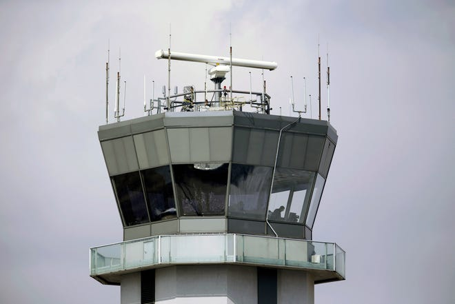 This March 12, 2013, file photo shows the air traffic control tower at Chicago's Midway International Airport. Federal regulators have not taken adequate steps to protect computer systems on airliners from hackers, a government watchdog agency reported.