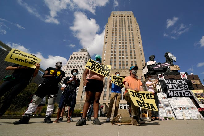 Protesters hold signs outside city hall Thursday, Oct. 8, 2020, in Kansas City, Mo., demanding the resignation of an officer who knelt on the back of nine-months-pregnant Black woman, Deja Stallings, while arresting her the previous week, and Police Chief Rick Smith. (AP Photo/Charlie Riedel) ORG XMIT: MOCR114