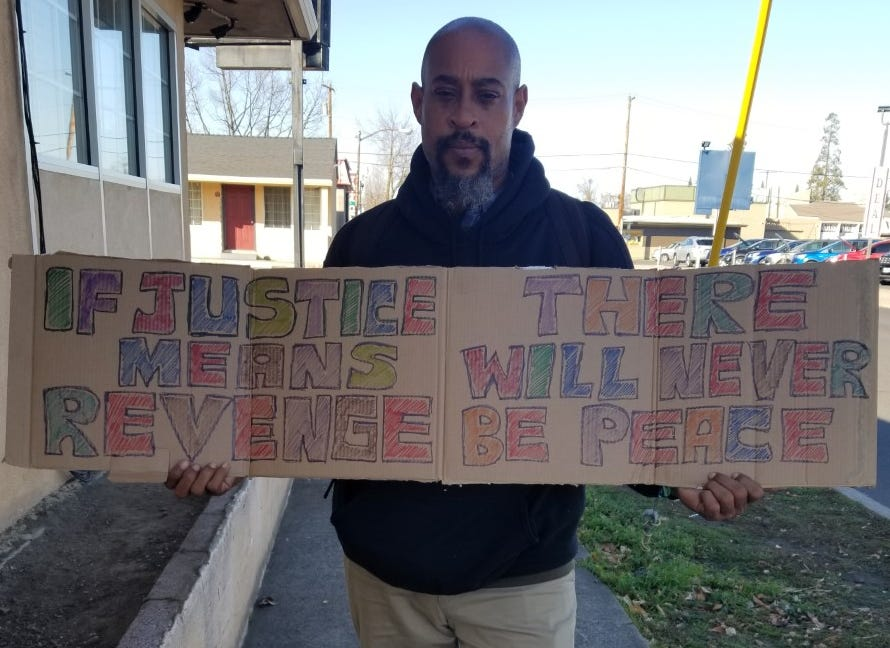 KokayiNosakhere holds a sign he made for the birthday of Martin Luther King Jr. He said he hoped his message would resonate with people no matter their skin color.