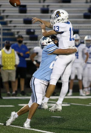 Louisville defender Carson Rode, left, wraps up ND-CL quarterback Jacob Koenig as he dumps a pass during first-round football tournament action at Louisville stadium Friday night, October 9, 2020.