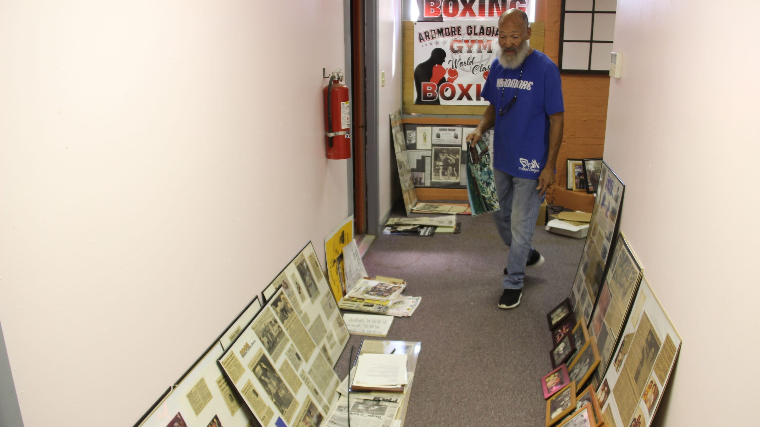 Garry Raymond walks down a hallway in Gladiator's Gym filled with more than 40 years of press clippings from fighters he's trained.