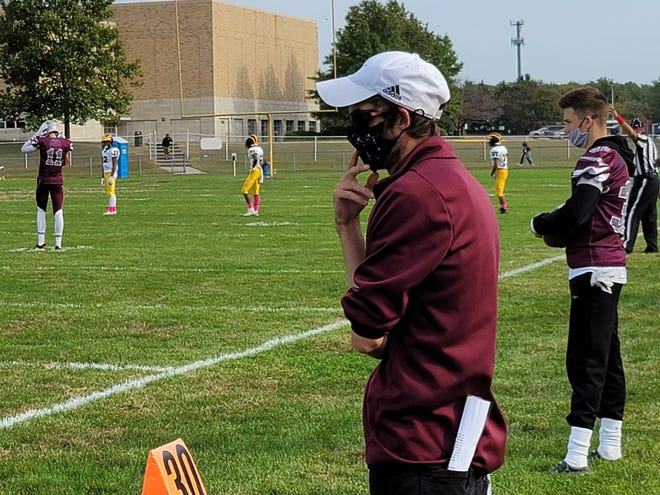 First-year Holy Cross coach T.J. Maderia looks out at his kickoff return team.