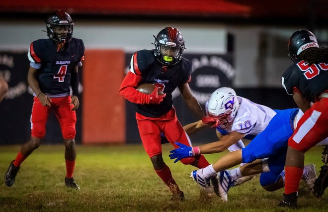 Aliquippa's Vernon Redd gets around Chartiers Valley's Sam Pocci for yards in the second quarter Friday night.