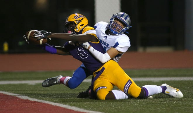 OLSH's Ziggy McIntosh (6) attempts to reach across the goal line while Union's Anthony Nealy (24) attempts to hold him back Friday night at Moon Area High School.