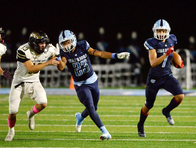 Central Valley's Jayvin Thompson (7) picks up some yards as Stephon Hall (25) blocks Keystone Oaks' Logan Shrubb during Friday night's game at Central Valley High School.