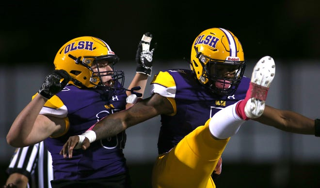 OLSH's Jaymar Pearson, right, celebrates with fellow teammate Gavin Tonery, left, after scoring a touchdown during the first half of Friday night's game against Union at Moon Area High School.