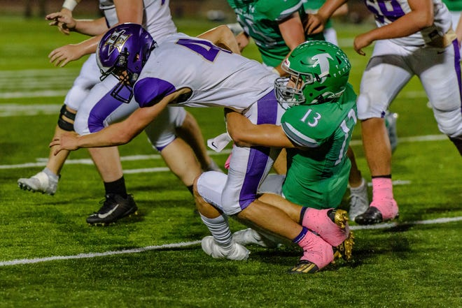 Hallsville quarterback Tyger Cobb (4) is stopped by Blair Oaks' Carson Prenger (13) during a game Friday night at Blair Oaks High School.