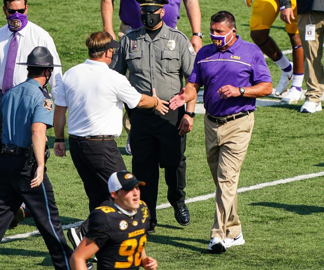 LSU Tigers head coach Ed Orgeron shakes hands with Missouri Tigers head coach Eliah Drinkwitz after Missouri's win at Faurot Field on Saturday.