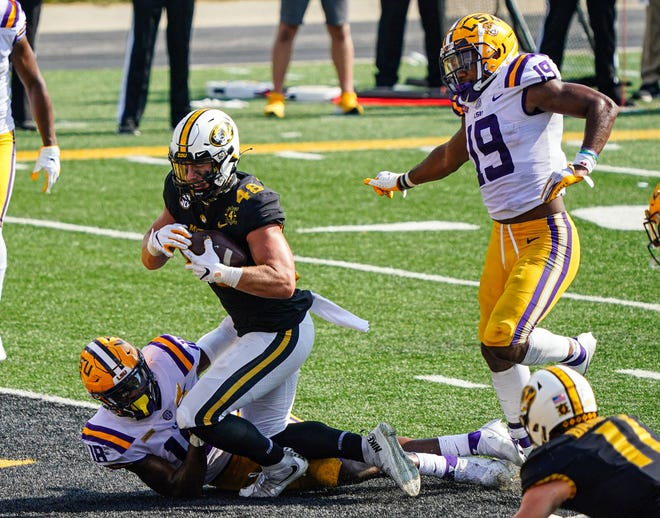 Missouri tight end Niko Hea (48) scores a touchdown against LSU linebackers Damone Clark (18) and Jabril Cox (19) during a Southeastern Conference game Saturday at Faurot Field.
