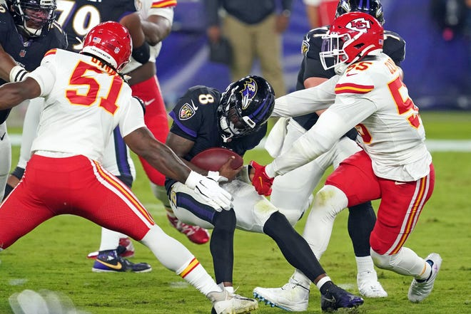 Kansas City Chiefs defensive ends Frank Clark (55) and Mike Danna (51) pressure Baltimore Ravens quarterback Lamar Jackson (8) during a game Sept. 20 at M&T Bank Stadium in Baltimore.