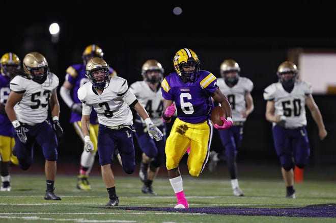 Reynoldsburg's Daniel Broomfield (6) runs away from a host of Lancaster defenders in the second quarter of the Raiders' 53-19 first-round playoff win on Friday. Kyle Robertson/Columbus Dispatch