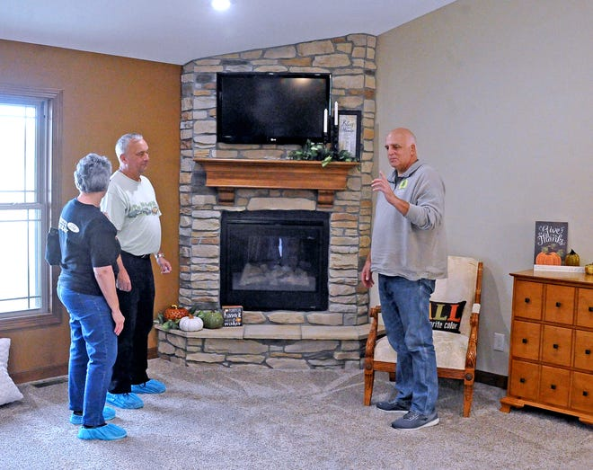 Mary and Bob Moomaw listen as Bob Wiles of Aspen Building Company shows them the corner fireplace at 1740 W. Smithville Western Road, Wooster.
