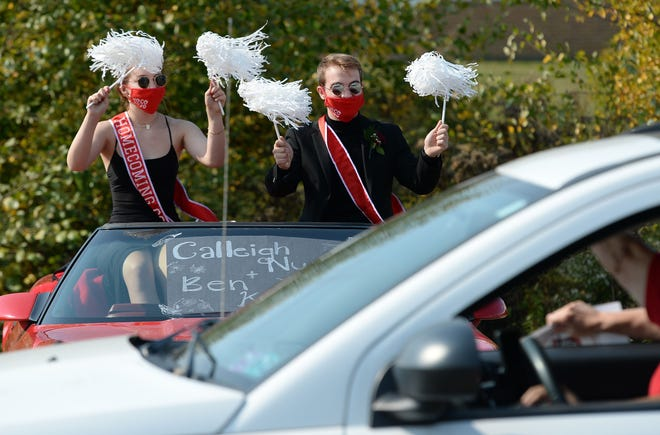 Calleigh Nurse, 17, and Ben Kalmey, 18, members of the General McLane homecoming court, greet motorists Saturday during the General McLane High School homecoming parade.